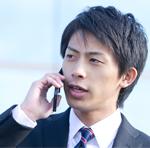 外出先から携帯電話で社内へ電話連絡をする営業マンのイメージ