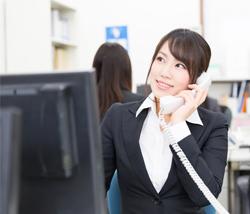 外出営業マンから外線電話連絡を受ける女性社員のイメージ