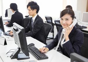 オフィスでビジネスフォンの受話器を持ち笑顔の女性イメージ