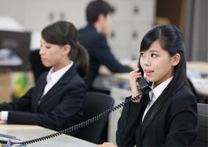 オフィスデスクでビジネスフォン受話器を持ち通話(会話)している女性イメージ
