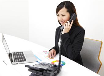 笑顔で会社の電話(ビジネスフォン)に対応する女性イメージ