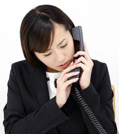 電話に出たはいいが、相手の声が聞き取りづらくパニックになっている女性イメージ