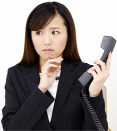 片手に受話器を持ち「苦手な電話対応は慣れるしかない」と思い込み困って悩んでいる女性イメージ